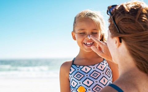 woman putting a dollop of sunscreen on little girl's nose