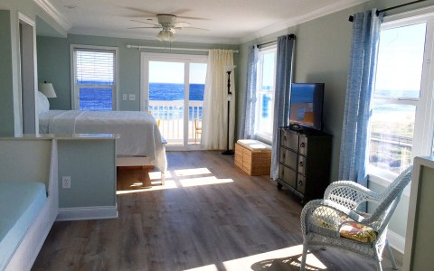 Room with wooden floors, tv and view to ocean