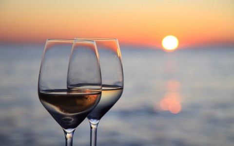 Wine glasses with sun setting in the back