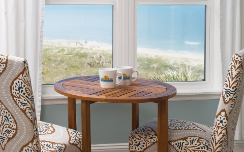 Small table with chairs next to window with ocean view