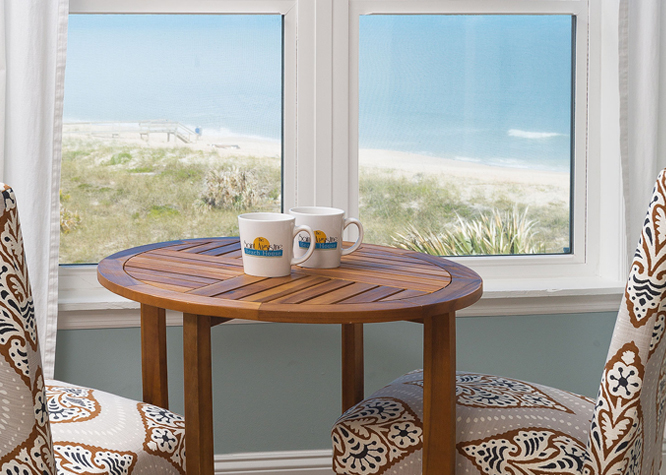 Two chairs next to window with ocean view