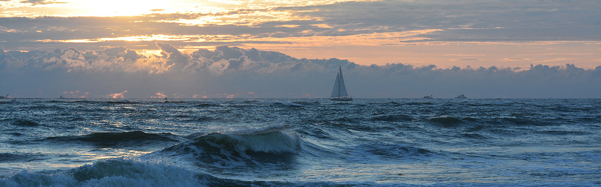 Vast ocean with sailboat in the distance
