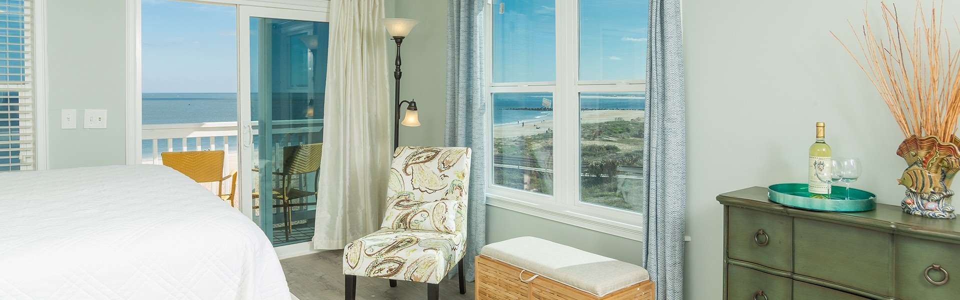 Room with chair next to private balcony with ocean view