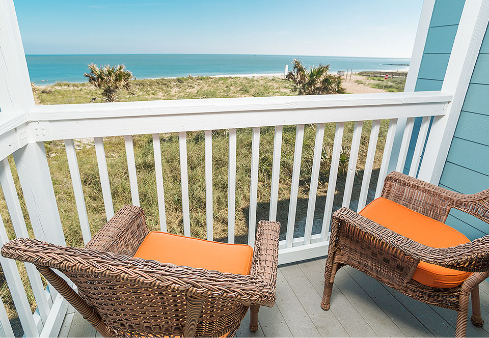Two chairs on private room balcony overlooking ocean
