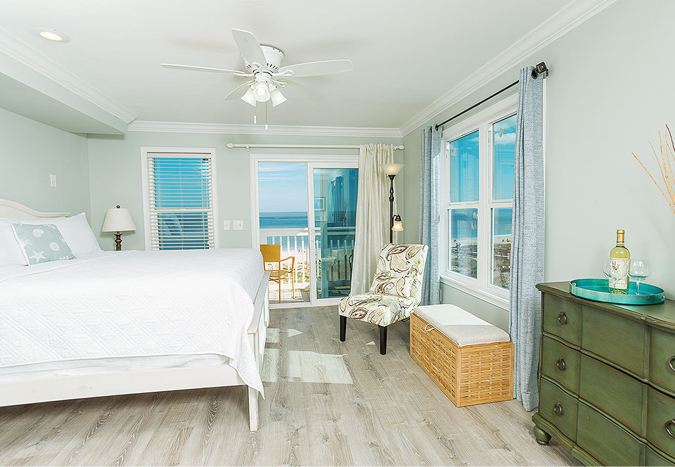Room with king bed, dresser and chair next to window with ocean view
