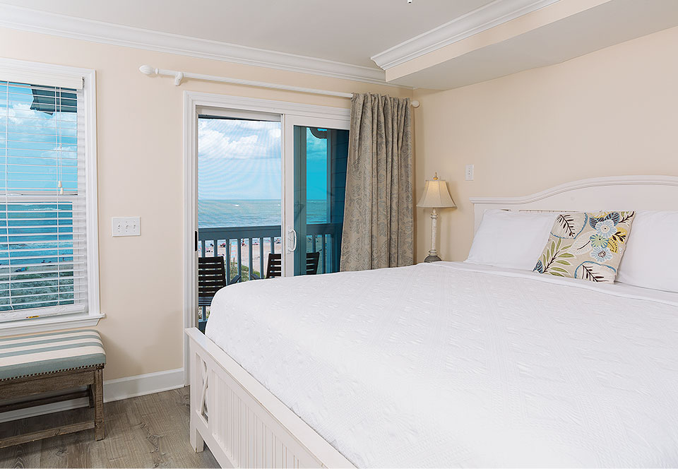 Room with king bed next to window with ocean view