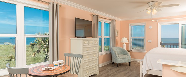 Room with dresser and dining table next to window with ocean view