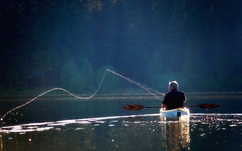 man fishing on kayak