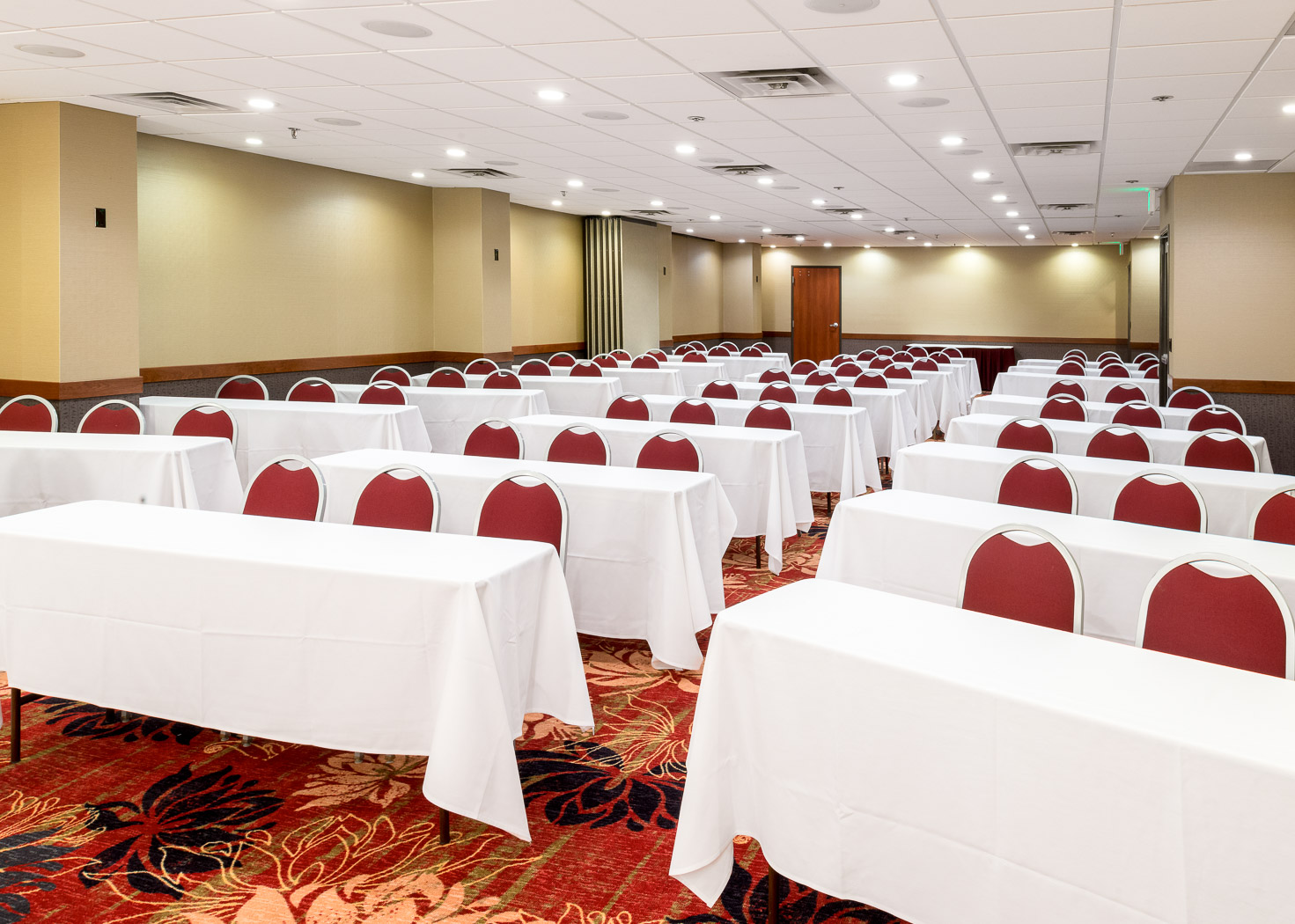 Meeting Room with tables set up with white table cloths and red chairs