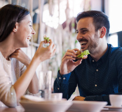 man and woman eating and smiling at each other