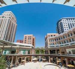 Outdoor courtyard looking up to tall buildings against a blue sky