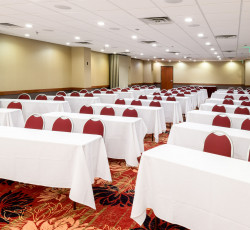 Meeting room setup classroom style tables with white tablecloths and red chairs