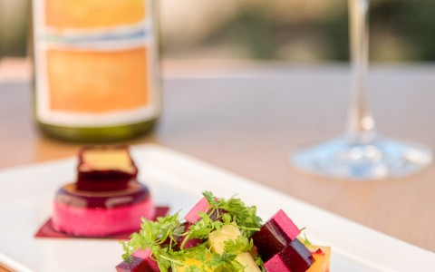 a plate with a summer salad and a glass of white wine