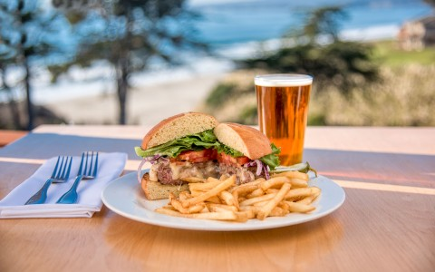 a burger with fries and a beer