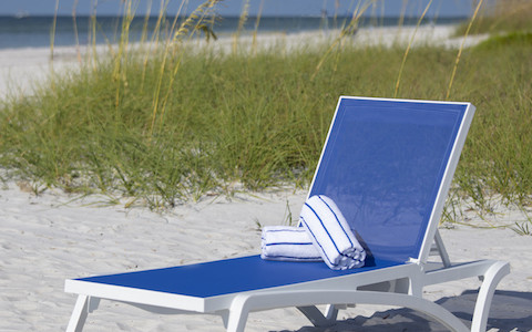 Blue beach lounger sitting on white sandy beach