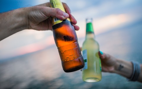 Couple toasting with beer bottles on beach