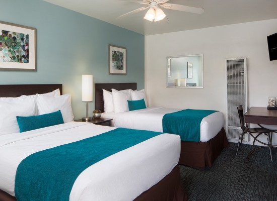 Guest room with two beds with teal accents