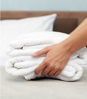 hands setting down folded white towels