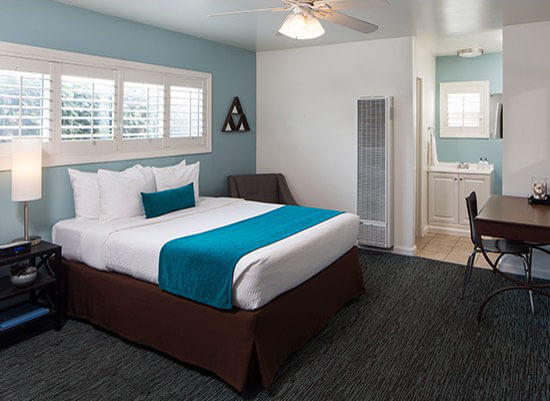 Guest room with bed with teal accent against blue wall
