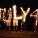 Children writing July 4th in the air with sparklers