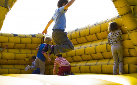 Kids bouncing on giant yellow inflatable