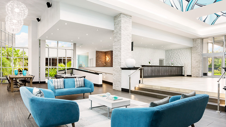 Bright Lobby with Large Windows, aqua accent sofas & white decor
