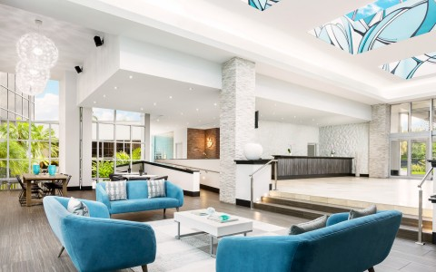 Hotel lobby space with white decor & aqua accent couches