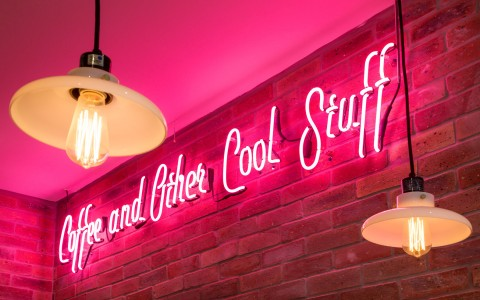 Pink neon signs that reads coffee and other cool stuff