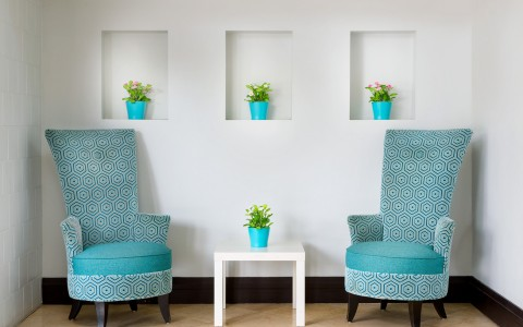 White wall & table with accent aqua chairs & flower pots