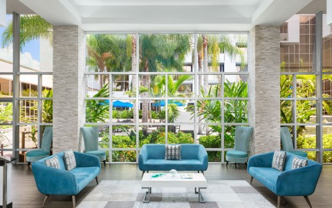 Lobby seating area with aqua accent couches & large window panel exposing greenery