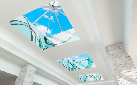 Rooftop windows in hotel lobby with wavy aqua glass designs