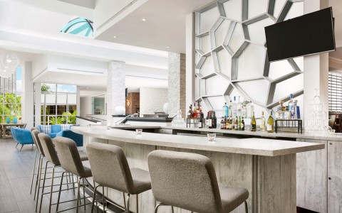 Hotel bar with padded stools & liquor bottles