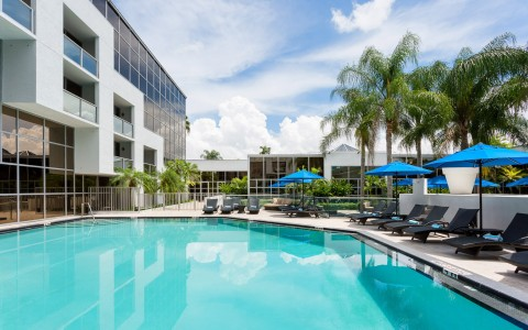 Hotel pool with black loungers & blue umbrellas