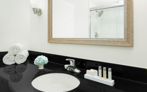 Bathroom sink with black marble counter, rolled towels & mini shampoo bottles