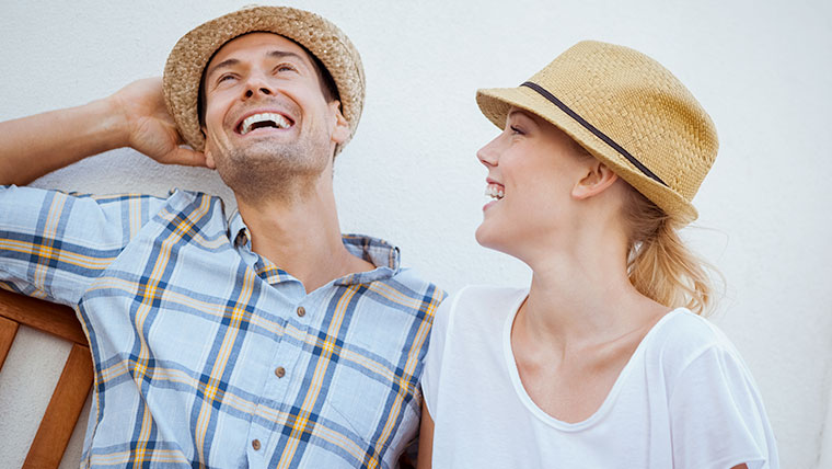 Couple wearing hats while laughing and smiling