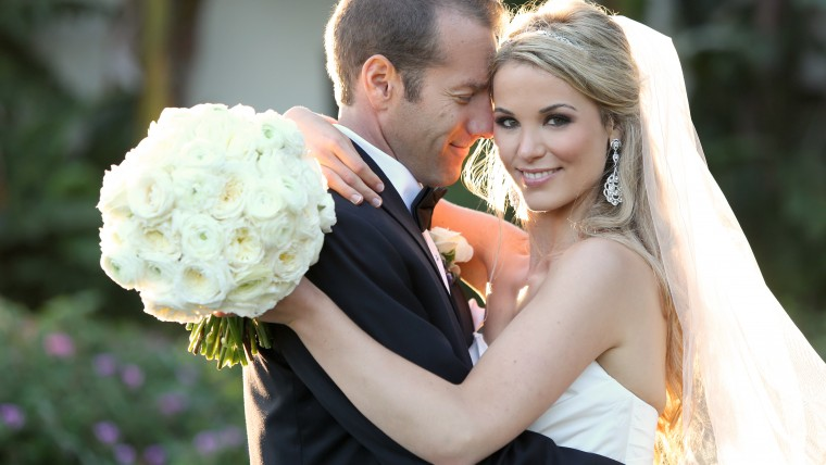 Bride hugging Groom and Holding white rose bouquet