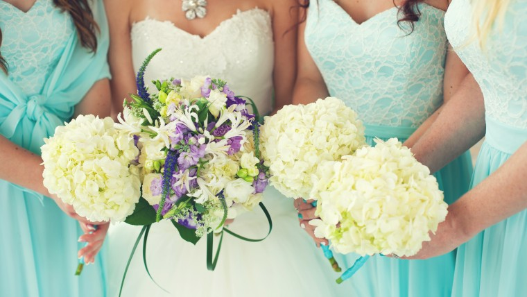 Close up of bride & bridesmaids in aqua dresses holding flower bouquets
