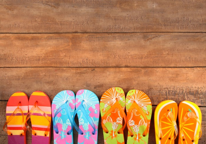 Four pairs of summer flip flops lined up on wood