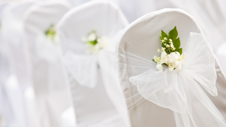 Chairs wrapped in white cloth, tulle & white rose