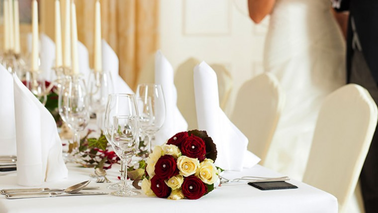 Table set for wedding with white decor & bouquet of roses