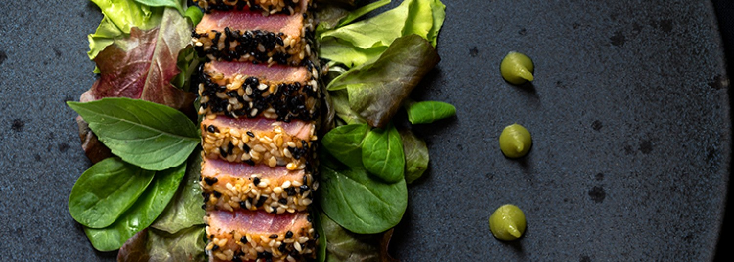 Two meals on table with bottle of wine with view of ocean