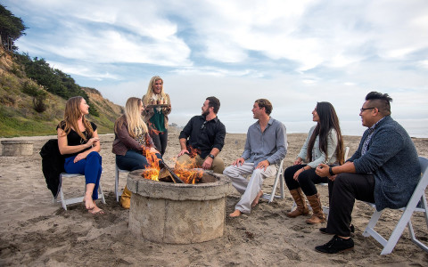 Group of people gathered around fire pit on the sand