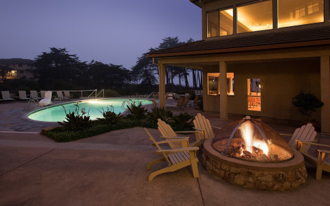 Chairs around fire pit next to pool