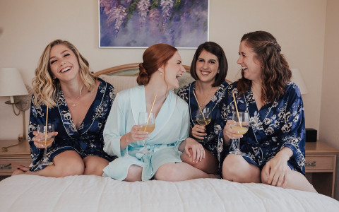 Group of woman in robes having drinks on bed