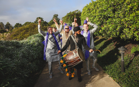 Group of people following man playing large drum through greenery