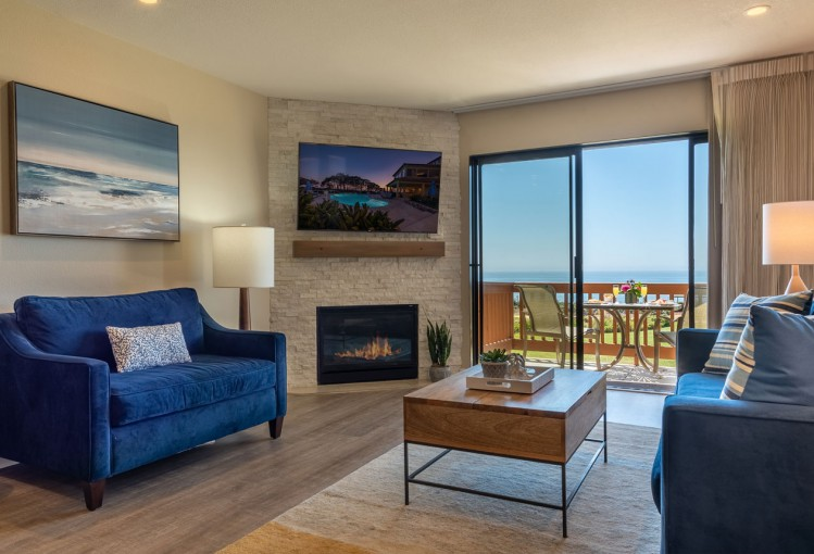 view of suite with blue sofas tv and ocean view