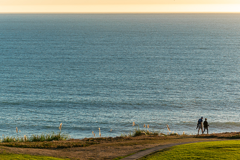two people walking on a cliff overlooking the ocean
