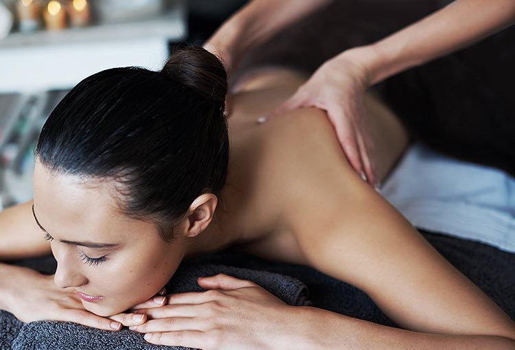 Woman laying down on her stomach getting massage