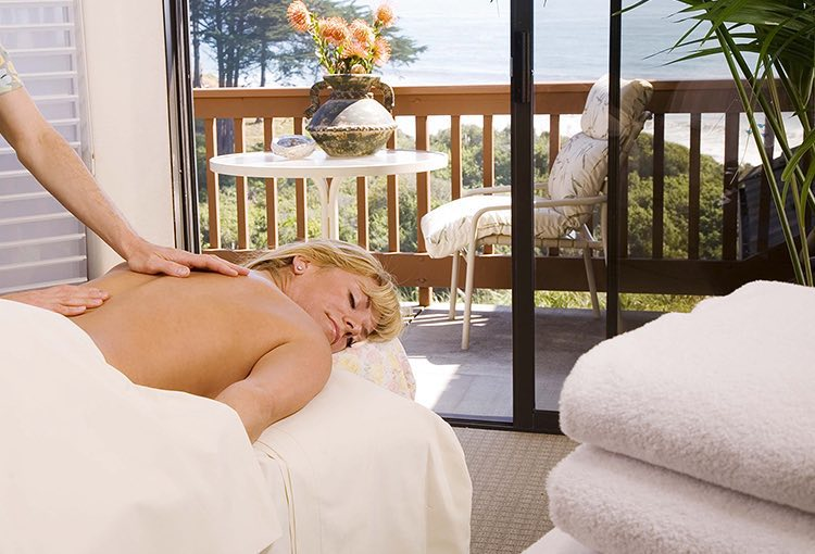Woman laying down on bed next to balcony getting massage