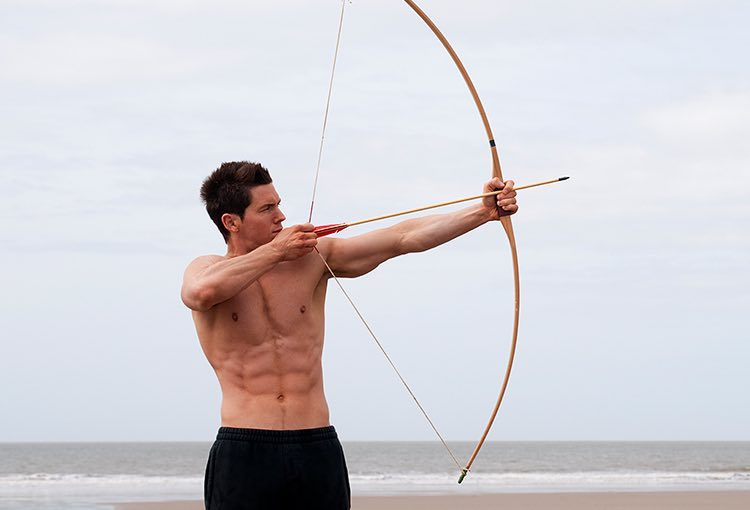 Man using bow and arrow on the beach